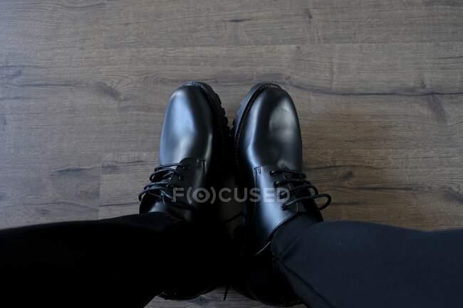 Pés masculinos em casual limpo par de botas pretas no chão de madeira — Fotografia de Stock