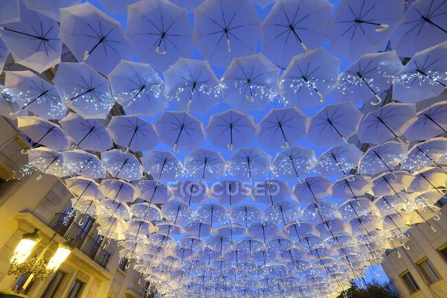 From below of white decorative umbrellas and burning garlands covering city walkway in twilight — Stock Photo
