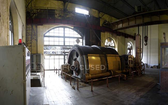 Промисловий круглий апарат з металевим механізмом, що знаходиться всередині безлюдних розбавлених промислових майстерень з легкими стінами і великими арочними вікнами. — стокове фото