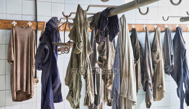 Брудні шахтарі висять на гачках у роздягальні. — стокове фото