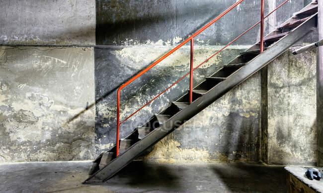 Вид сбоку металлической лестницы с красными перилами — стоковое фото