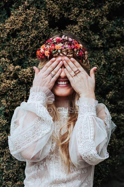 Encantada joven hembra en vestido de novia y corona floral sonriendo y cubriendo los ojos mientras está de pie cerca de arbusto verde en el jardín - foto de stock