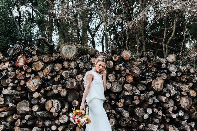 Cultivo novia de pie cerca de pila de troncos - foto de stock