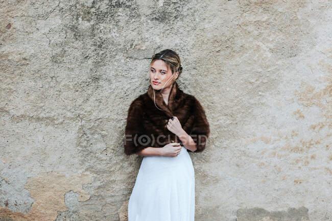 Junge Frau in weißem Kleid und kurzem Pelzmantel schaut weg, als sie am Hochzeitstag in der Nähe einer verwitterten Hauswand steht — Stockfoto