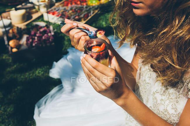 Desde arriba vista de la joven anónima en elegante vestido de novia blanco comiendo delicioso postre de fresa dulce con cuchara durante el almuerzo al aire libre - foto de stock