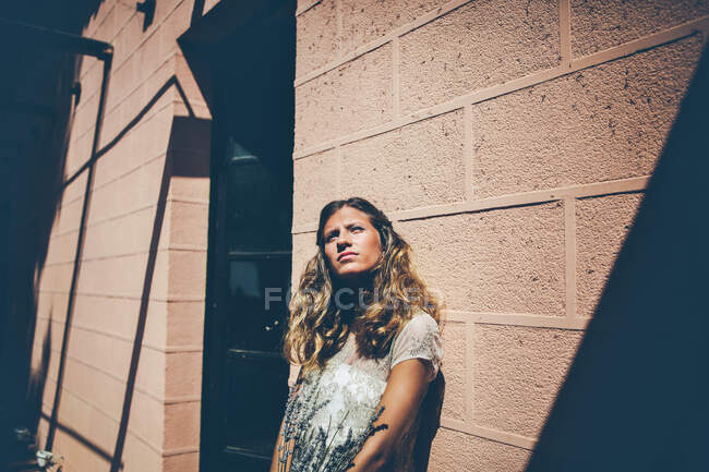 Young thoughtful lady in elegant white dress standing near wall with bouquet of lavender and looking up dreamily — Stock Photo