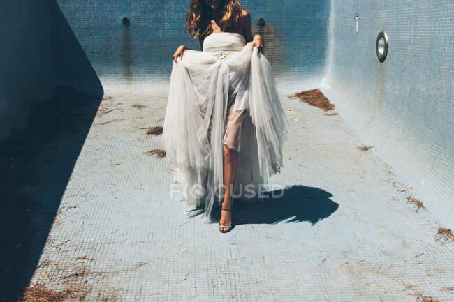 Joyeux jeune mariée anonyme en robe de mariée blanche élégante dansant sensuellement dans la piscine sale vide le jour ensoleillé pendant la fête romantique — Photo de stock