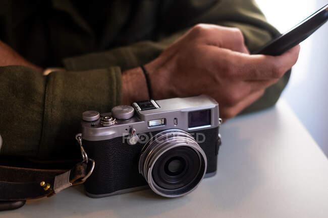 Кадрирование анонимный фотограф в повседневной одежде с помощью смартфона, сидя за белым столом с ретро-пленкой камеры на размытом фоне — стоковое фото