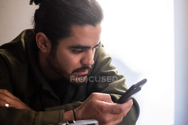 Ethnic handsome pensive bearded crop male in casual wear browsing smartphone and looking at screen while sitting against light background — Stock Photo