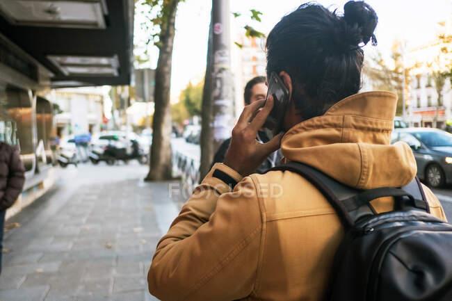 Vista trasera de hombre anónimo en chaqueta de otoño con pelo largo y oscuro en bollo hablando en smartphone mientras camina por la calle en la ciudad con mochila — Stock Photo