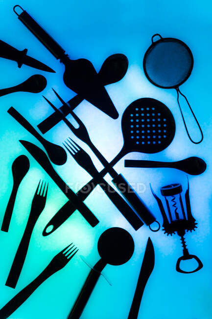 Top view of various essential cooking tools and cutlery placed chaotically on illuminated blue background — Stock Photo