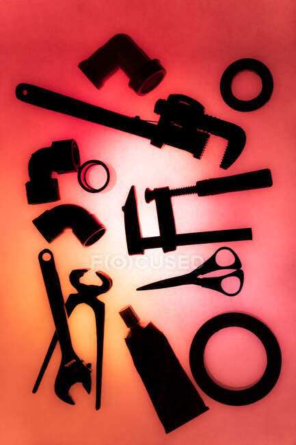 Top view composition of various instruments and materials for sanitary works arranged on illuminated red background — Stock Photo