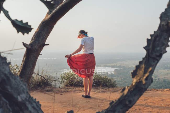 Вид сзади на женщину в футболке и юбке, стоящую на песчаном холме и покрывающую лицо, наслаждаясь закатом и путешествуя по Шри-Ланке — стоковое фото