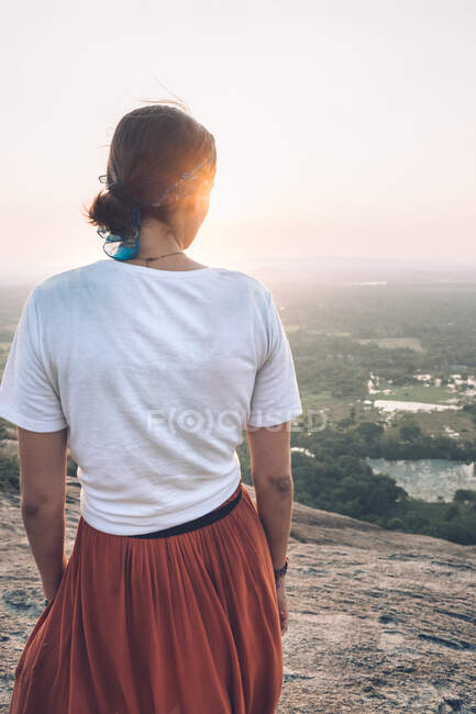 Back view of unrecognizable traveling woman in casual clothes and bandana admiring scenic landscape during vacation in Sigiriya while standing in back lit and looking away — Stock Photo