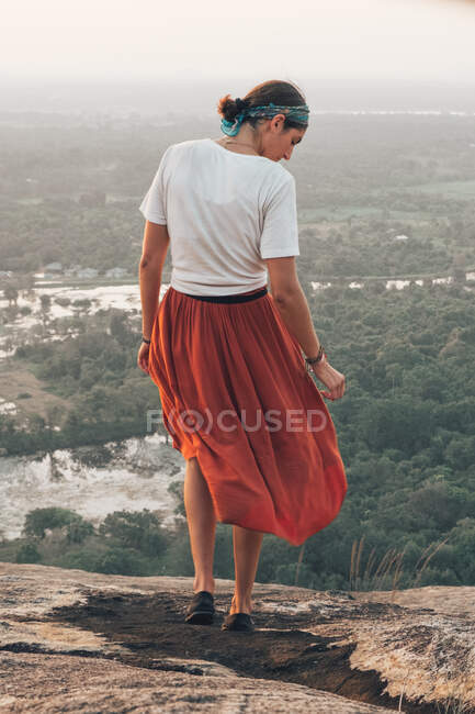 Back view of unrecognizable traveling woman in casual clothes and bandana admiring scenic landscape during vacation in Sigiriya — Stock Photo