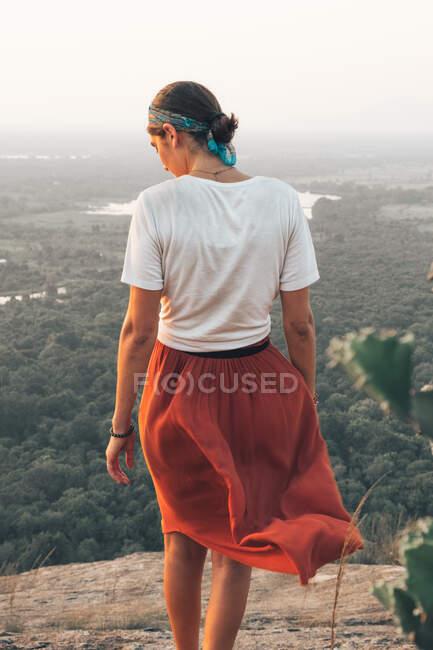 Vista posterior de una mujer viajera irreconocible con ropa casual y pañuelo admirando el paisaje escénico durante las vacaciones en Sigiriya - foto de stock