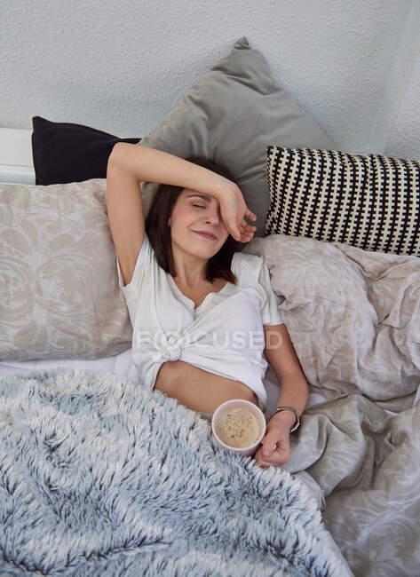 Desde arriba de la mujer joven en ropa de dormir acostado en la cama y disfrutar de café caliente mientras descansa en el acogedor dormitorio en casa - foto de stock