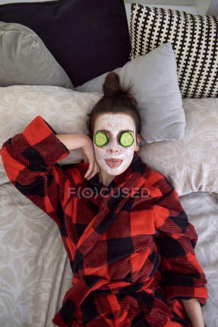 Von oben junge Frau im karierten Bademantel mit weißer Gesichtsmaske und Gurkenscheiben auf Augen, die auf dem Bett liegen, während sie es sich zu Hause gemütlich macht — Stockfoto