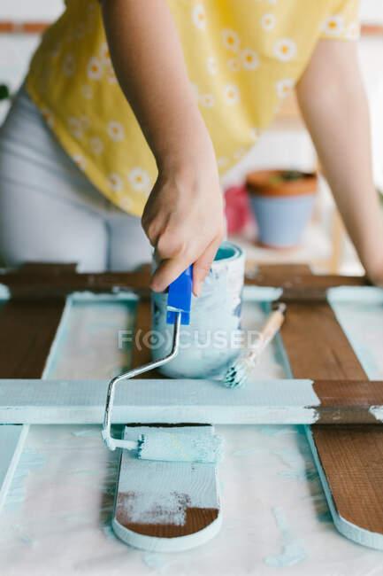 Крупный план женской руки с помощью ролика краски для восстановления забора. — стоковое фото