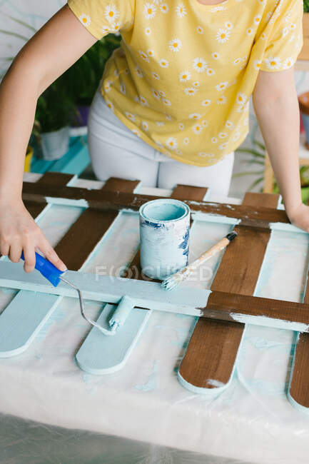 Close-up view of a person using a paint roller for restoring an old fence. — Stock Photo