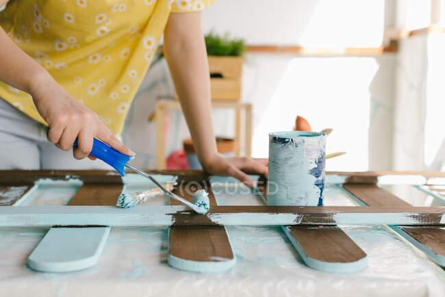 Chica rubia joven está utilizando un rodillo de pintura para restaurar una vieja cerca. - foto de stock