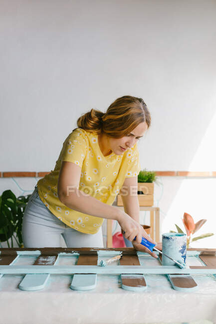 Young blonde woman painting an old fence for her terrace — Stock Photo