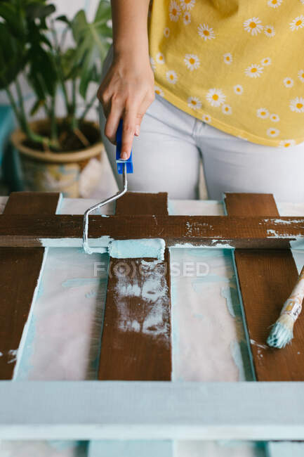 Девушка восстанавливает забор, рисуя деревянные полоски. Крупный план. — стоковое фото