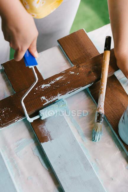 Погляд на руки людини, що завершує реставрацію старого паркану.. — стокове фото
