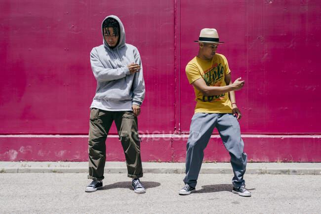Dos jóvenes bailando cerca de una pared rosa en la calle - foto de stock
