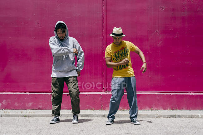 Two young men dancing near to a pink wall on the street — Stock Photo