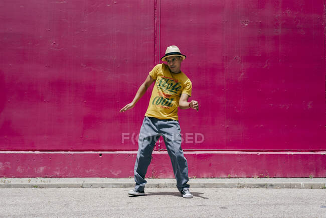 Young hispanic men dancing near to a pink wall on the street — Stock Photo