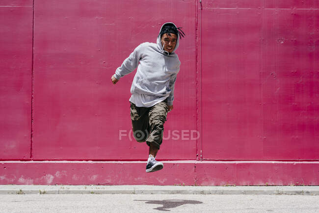 Young hispanic men jumping near to a pink wall on the street — Stock Photo