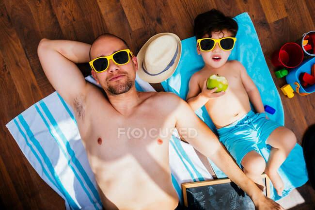 De cima vista de menino alegre em óculos de sol amarelos e azul swimwear sorrindo enquanto alimentando pai maçã deitada em toalhas juntos tendo praia em casa — Fotografia de Stock
