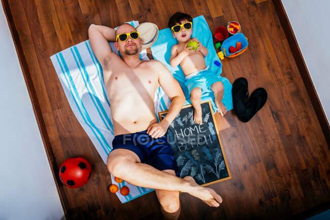 Dall'alto di padre e figlio positivo in occhiali da sole gialli e costumi da bagno sdraiati sul pavimento su asciugamani e sognando vacanze estive sulla spiaggia durante la quarantena — Foto stock
