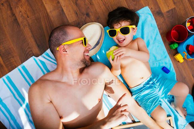 Von oben sieht man einen fröhlichen Jungen mit gelber Sonnenbrille und blauer Badebekleidung, der lächelt, während er Vater Apfel füttert, der auf Handtüchern liegt und zu Hause am Strand liegt. — Stockfoto