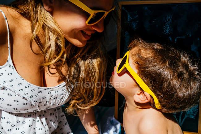 Seitenansicht von positiver Mutter in weißem Kleid und gelber Sonnenbrille, die Nasen berührt, mit Sohn in gleicher Sonnenbrille im hellen Sonnenlicht — Stockfoto