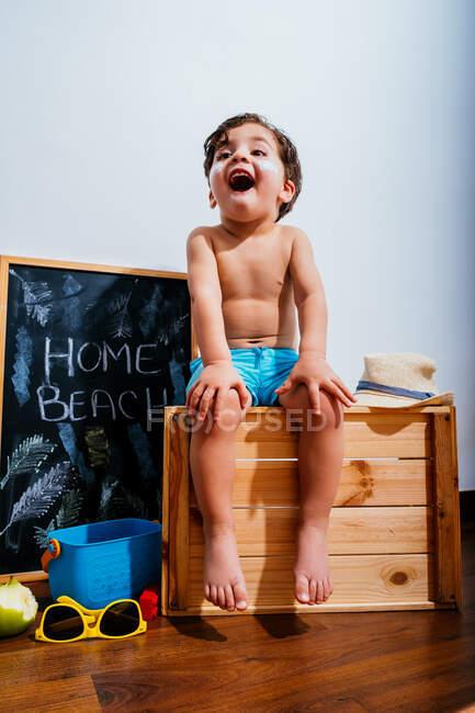 Menino alegre em calções de banho azuis sentado na caixa de madeira e sonhando com fim de semana na praia durante o auto-isolamento — Fotografia de Stock
