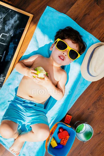 Desde arriba vista de niño alegre en gafas de sol amarillas y trajes de baño azules comiendo manzana mientras está acostado en la toalla en el suelo tener casa playa en cuarentena - foto de stock
