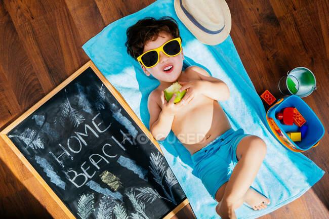 De cima vista de menino alegre em óculos de sol amarelos e azul swimwear comer maçã enquanto deitado em toalha no chão tendo praia em casa em quarentena — Fotografia de Stock