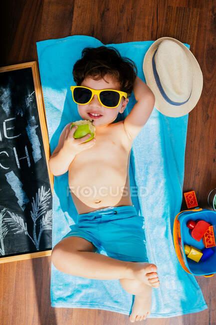 Blick von oben auf einen fröhlichen kleinen Jungen in gelber Sonnenbrille und blauer Badebekleidung, der Apfel isst, während er auf einem Handtuch auf dem Boden liegt und einen Hausstrand unter Quarantäne hat — Stockfoto