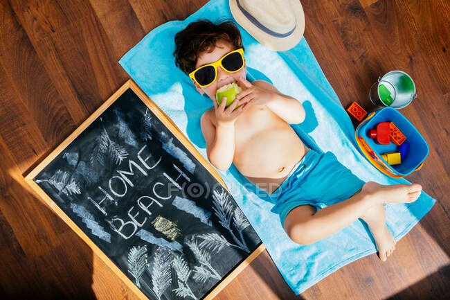 From above view of cheerful little boy in yellow sunglasses and blue swimwear eating apple while lying on towel on floor having home beach on quarantine — Stock Photo