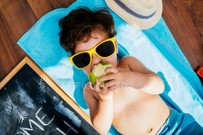 Зверху ви бачите веселого маленького хлопчика в жовтих сонцезахисних окулярах і блакитного плавця, який їсть яблуко, лежачи на рушнику на підлозі з домашнім пляжем на карантині. — стокове фото