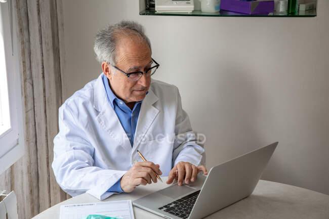 Senior medico di sesso maschile indossa abito medico seduto a tavola e parlare con il paziente tramite videochiamata sul computer — Foto stock