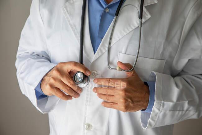 Tiro recortado de médico masculino vestindo vestido médico segurando estetoscópio — Fotografia de Stock