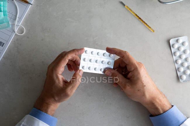 Mãos de médico masculino segurando pacote de pílulas — Fotografia de Stock