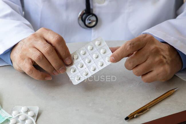 Hombre médico manos sosteniendo paquete de píldoras - foto de stock