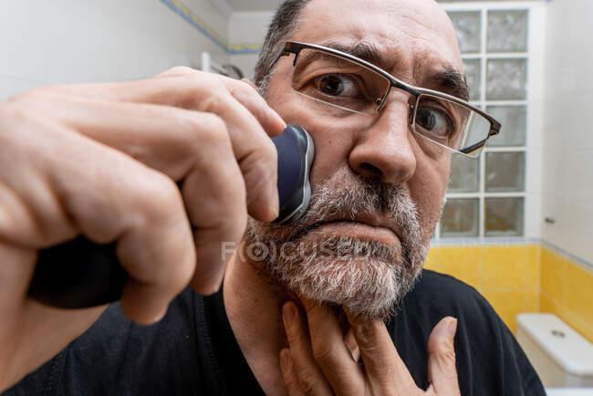 Homme barbu d'âge moyen dans les lunettes de rasage avec rasoir électrique — Photo de stock