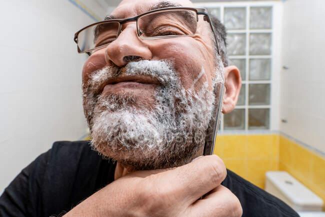 Bärtiger rasiert sich mit Rasiermesser — Stockfoto