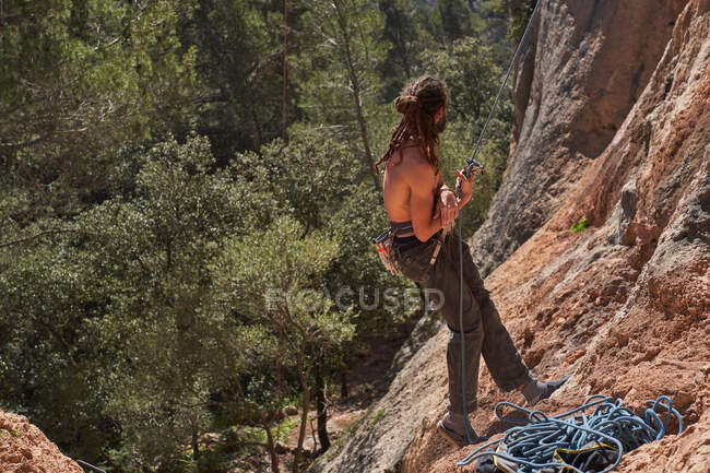 Side view of active bearded shirtless male climber standing on edge of cliff and holding rope in hands while looking away — Stock Photo