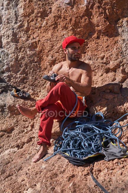 Alpinista masculino barbudo em sportswear vermelho sentado em solo rochoso perto de corda azul e usando sapatos de escalada antes de subir — Fotografia de Stock